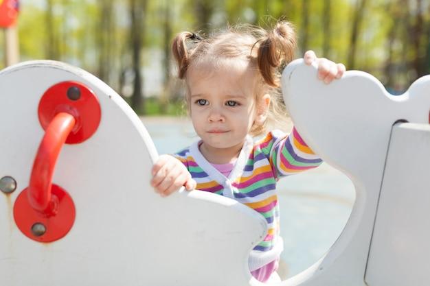 Uma menina com duas caudas está vestida com um casaco colorido listrado está jogando no playground