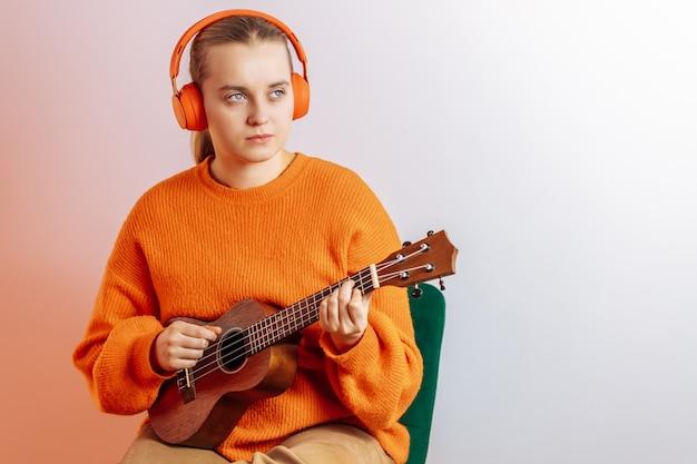 Uma menina com fones de ouvido toca ukulele