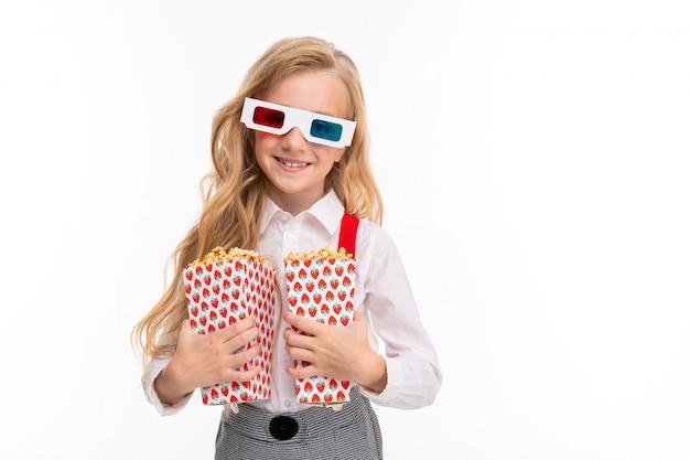 Uma menina com longos cabelos loiros em seus óculos 3-d com pipoca.