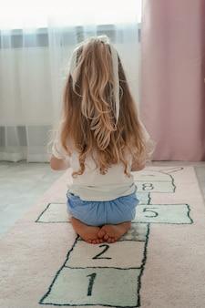 Uma menina com longos cabelos loiros está sentada de costas. cabelo bonito e espesso em uma criança. a loira brinca com brinquedos no quarto de seus filhos