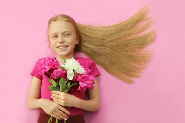 Uma menina com longos cabelos loiros sorri segurando peônias nas mãos