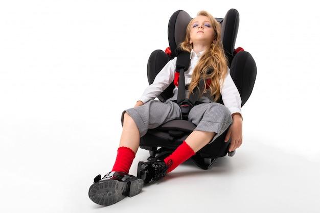 Uma menina com maquiagem e longos cabelos loiros dorme em uma cadeira de bebê de carro
