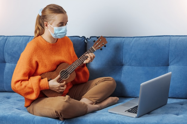 Uma menina com máscara médica aprende a tocar ukulele na quarentena