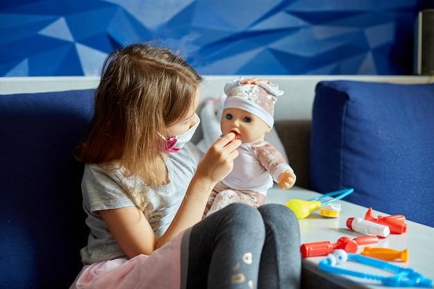 Uma menina com máscara médica se senta no sofá, faz o papel de médico, trata e escuta a boneca com um estetoscópio com máscara médica, em casa
