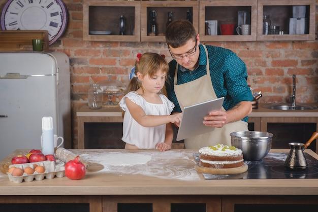 Uma menina com o pai na cozinha com um tablet digital está preparando o jantar