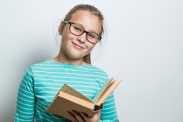 Uma menina com óculos está lendo um livro.