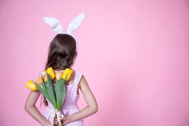 Uma menina com orelhas de coelho da páscoa segura um buquê de tulipas nas mãos atrás das costas em um estúdio rosa