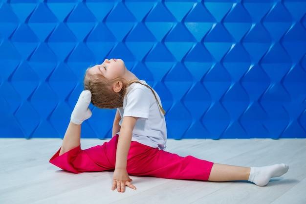 Uma menina com rabo de cavalo em uma camiseta branca sobre um fundo azul senta-se em barbante no chão e sorri. emoções infantis, foco de ocupação, diversão