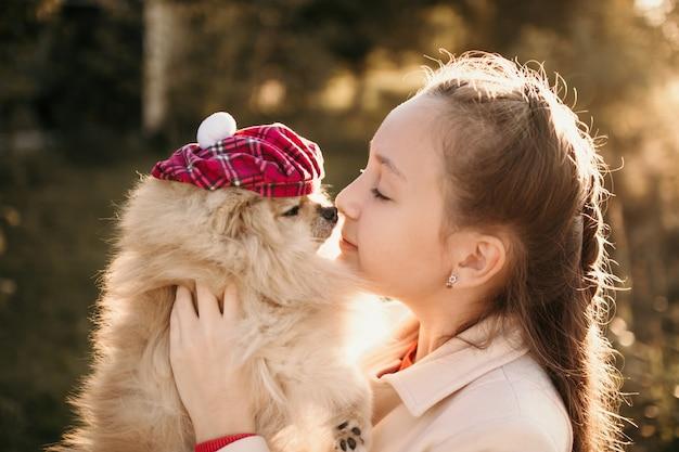 Uma menina com seu cachorro da pomerânia em uma boina quadriculada para passear na tarde de outono