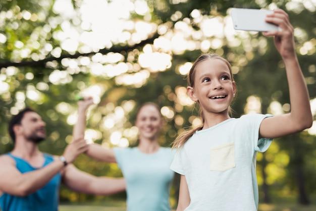 Uma menina com seus pais se diverte no parque.