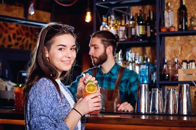Uma menina com sorrisos cocktail atrás do balcão no bar