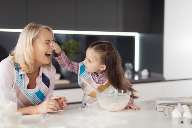 Uma menina com sua avó cozinha um bolo caseiro.