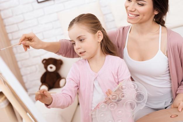 Uma menina com sua mãe pintar.