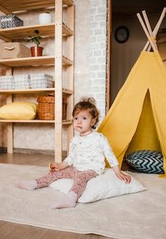 Uma menina com um biscoito na mão se senta no chão com uma cara pensativa. cabana amarela