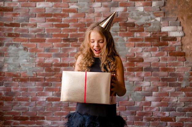 Uma menina com um boné de aniversário segura uma caixa de ouro e se alegra.