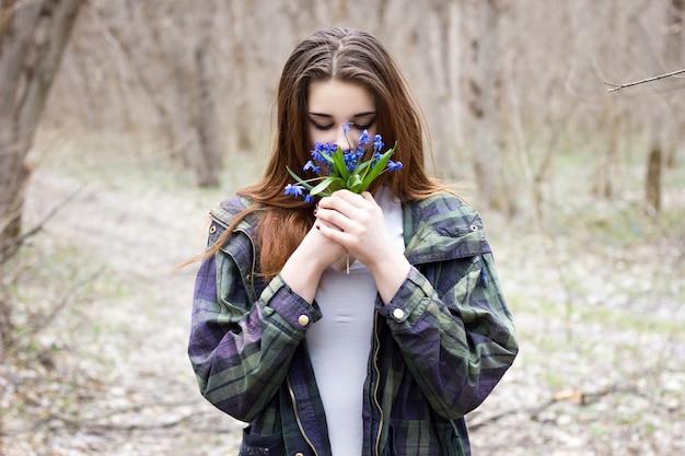 Uma menina com um buquê de flores silvestres azuis na natureza, uma menina bonita com flores da primavera