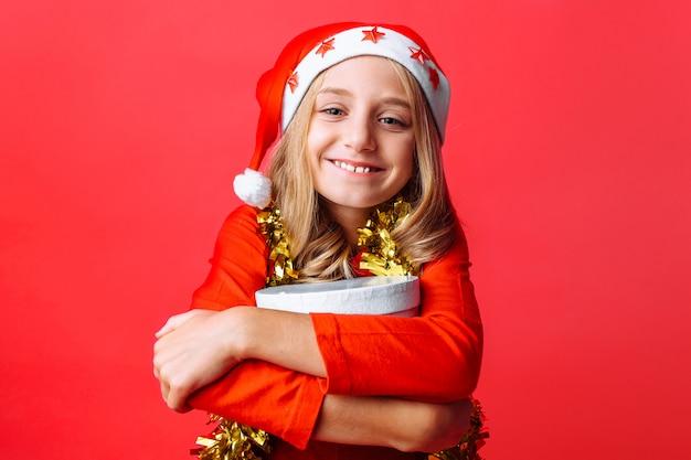 Uma menina com um chapéu de natal e com enfeites no pescoço