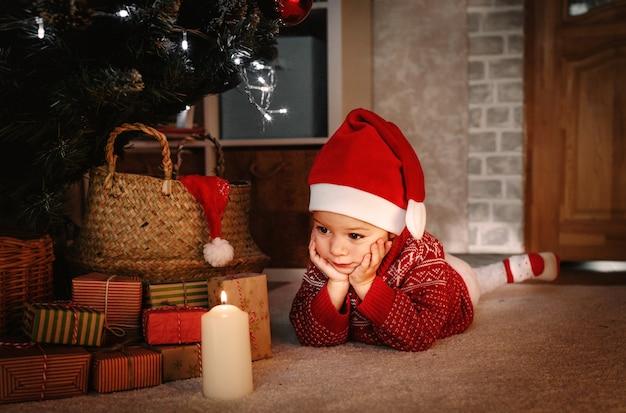 Uma menina com um chapéu de papai noel e um suéter vermelho olha para uma vela acesa debaixo da árvore