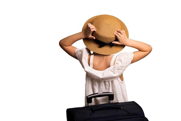 Uma menina com um chapéu e uma mala com bagagem, uma bolsa de viagem nas mãos olhando para a frente
