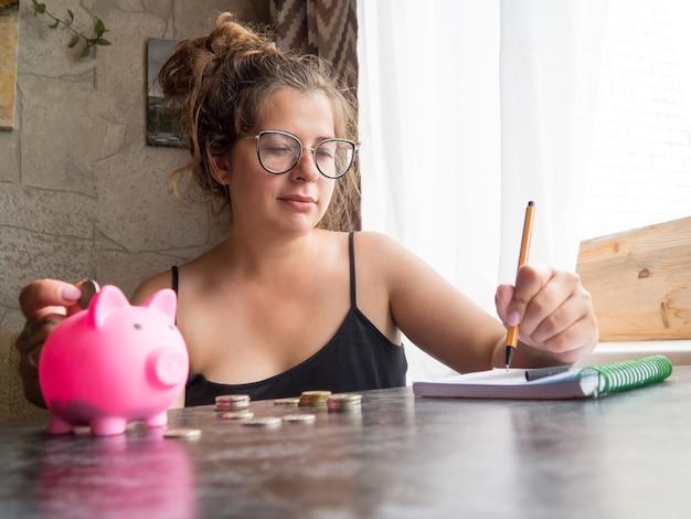 Uma menina com um cofrinho, ela não tem dinheiro, ela olha moedas e chora. conta despesas e utilidades, pobreza