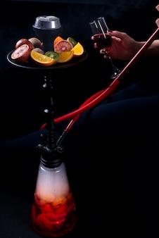 Uma menina com um copo de vinho nas mãos fuma um cachimbo de água