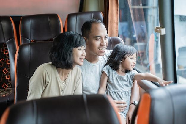 Uma menina com um dedo apontando para fora da janela enquanto seus pais estão sentados no banco do ônibus enquanto viaja