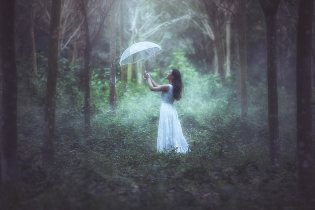 Uma menina com um guarda-chuva branco está na floresta.
