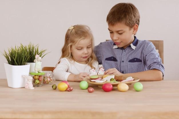 Uma menina com um irmão mais velho está sentado na mesa de férias e colocar biscoitos e ovos de páscoa