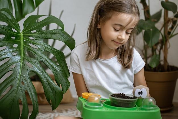 Uma menina com um kit de bebê para cultivar uma planta sozinha.