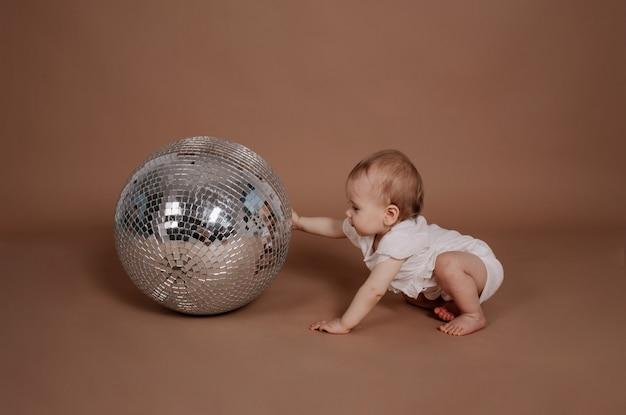 Uma menina com um macacão branco brinca com uma bola de discoteca prateada em um fundo bege com um lugar para o texto