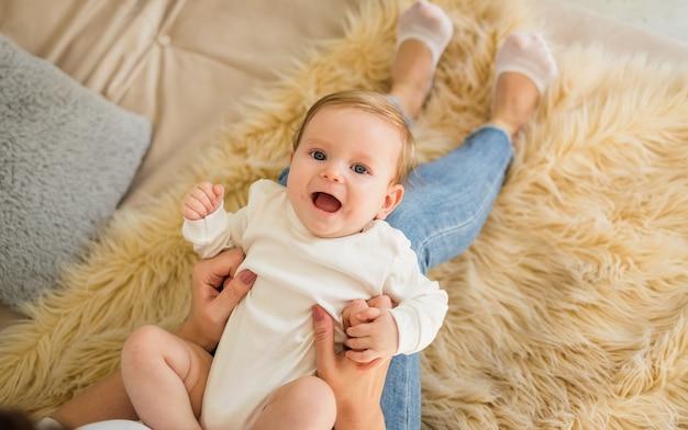 Uma menina com um macacão branco está deitada nos pés da mãe