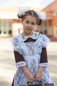 Uma menina com um uniforme escolar retrô e um avental branco caminha pela rua com uma pasta depois da escola