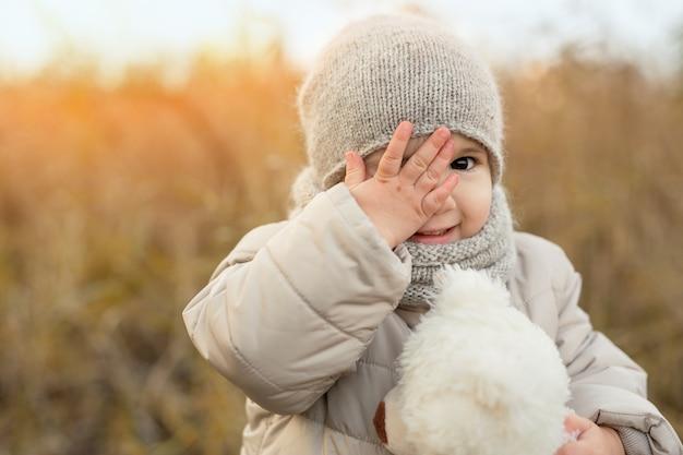 Uma menina com um ursinho macio cobre um olho com a mão e sorri docemente
