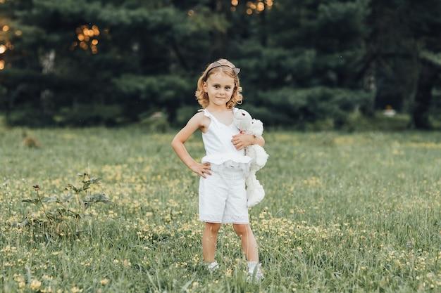 Uma menina com um urso branco na mina a céu aberto ao pôr do sol