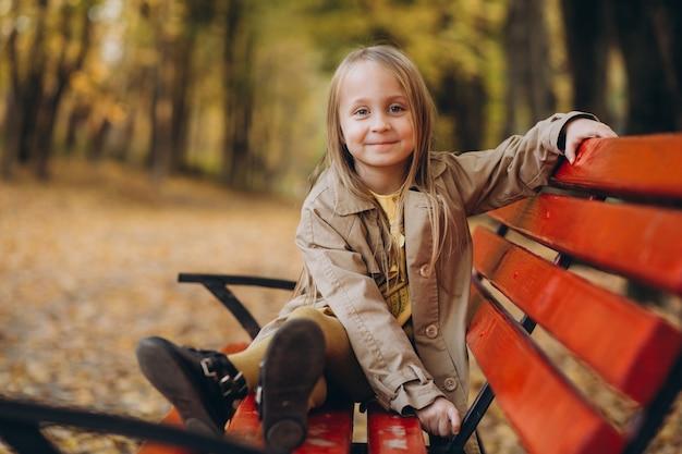 Uma menina com um vestido amarelo e um casaco bege caminha no outono park