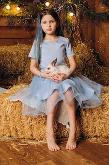 Uma menina com um vestido azul sentada em uma fazenda com um coelho páscoa e o conceito de agricultura