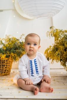 Uma menina com um vestido branco bordado sentado com buquês de mimosa