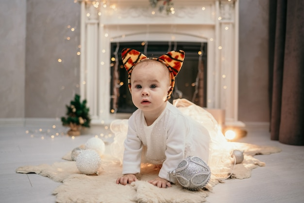 Uma menina com um vestido branco fofo e orelhas de tigre rasteja no tapete da sala