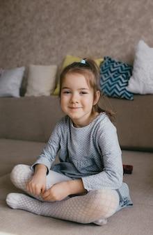 Uma menina com um vestido cinza senta no sofá e sorri