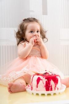 Uma menina com um vestido rosa de festa comendo um bolo doce