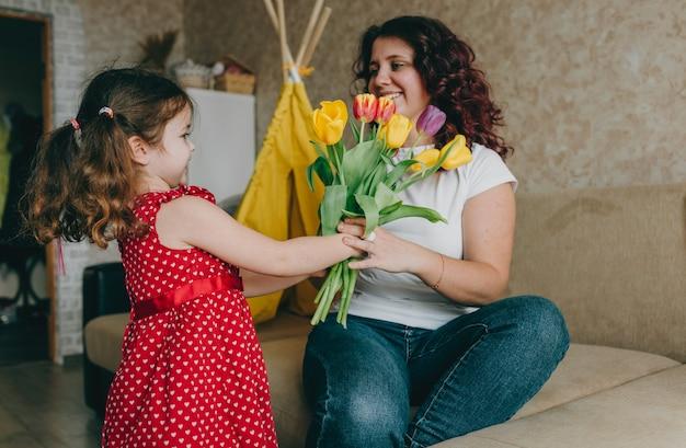 Uma menina com um vestido vermelho dá a uma mãe feliz um grande buquê de tulipas brilhantes. um presente para os pais.