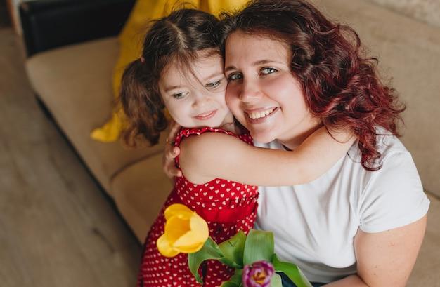 Uma menina com um vestido vermelho dá a uma mãe feliz um grande buquê de tulipas brilhantes.