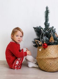 Uma menina com um vestido vermelho sentada perto de uma árvore de natal com brinquedos