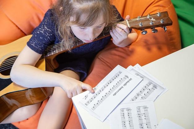 Uma menina com um violão aprende solfejo, partituras e teoria musical.