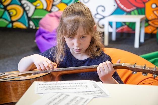 Uma menina com um violão aprende solfejo, partituras e teoria musical