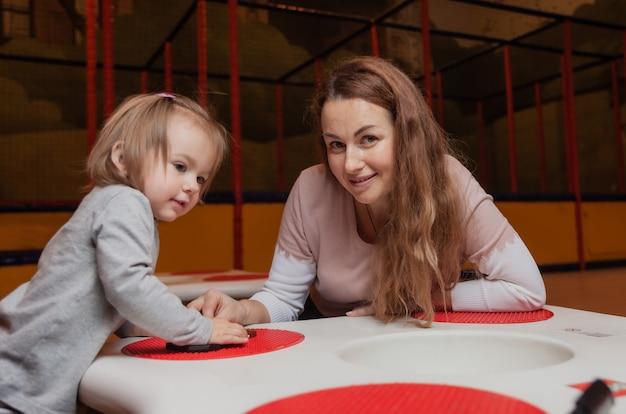 Uma menina com uma babá joga tijolos de brinquedo na mesa de um centro de entretenimento infantil