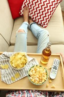 Uma menina com uma bandeja almoçando em um sofá, close-up