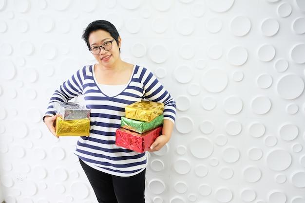 Uma menina com uma caixa de presente colorida. o local da festa é lindo para aproveitar a diversão de todos.