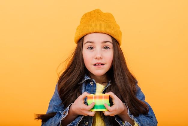 Uma menina com uma camisa multicolorida segura um brinquedo colante multicolor nas mãos
