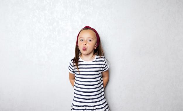 Uma menina com uma camiseta listrada com listras pretas e brancas posando na parede cinza fazendo caretas